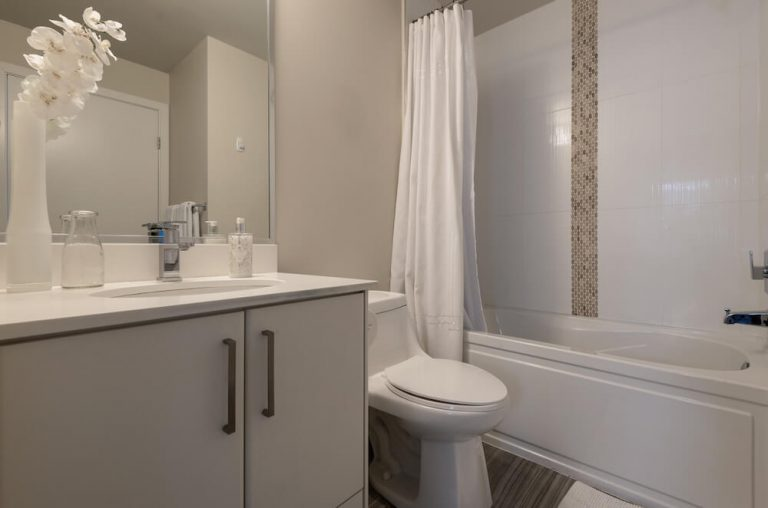 Remodeled Bathroom with Grey Cabinets White Toilet White Porcelain Bathtub White Tile