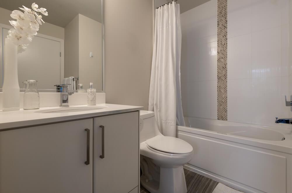 Remodeled Bathroom with Grey Cabinets White Toilet White Porcelain tub White Tile