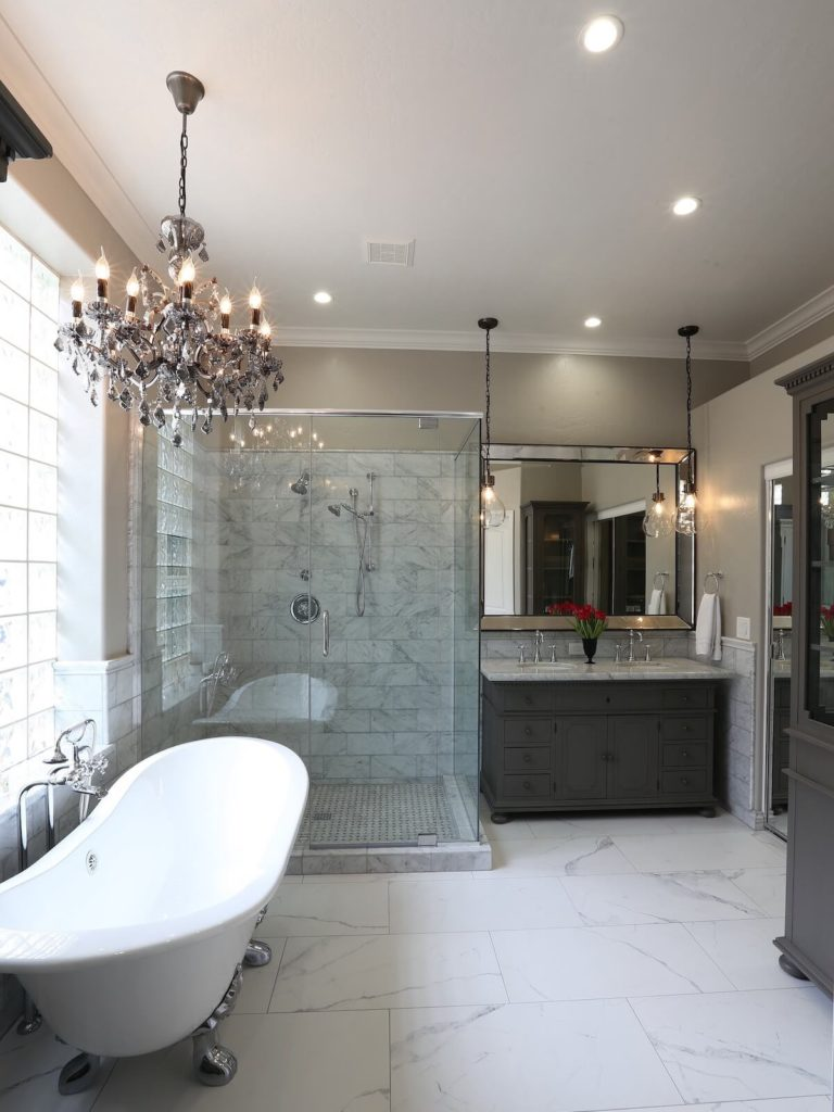 Bathroom Remodel Free Standing Bathtub Chrome Framed Glass Shower Doors Brown Cabinets Marble Tile Frosted Windows Chandelier Recessed Lighting Vanity