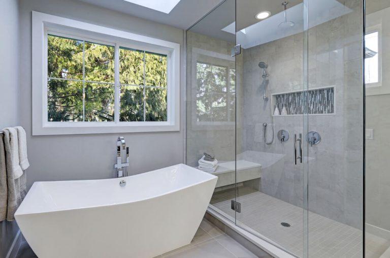 Bathroom remodel San Diego, standing tub, frameless glass, white trimmed windows, beige floor tile, chrome fixtures
