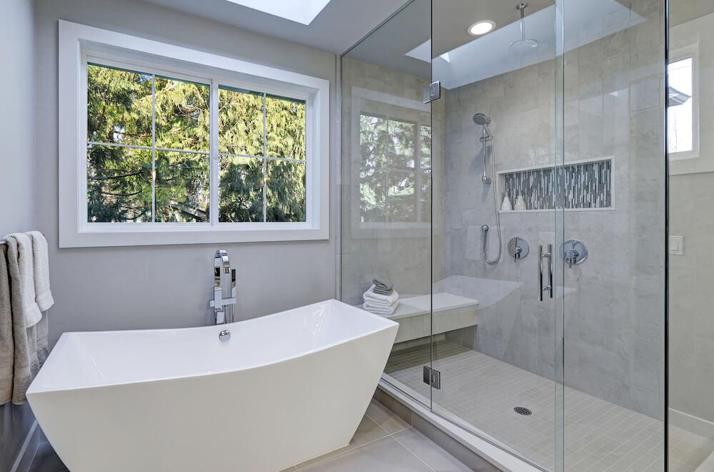 Bathroom remodel San Diego, standing tub, frameless glass shower, white trimmed windows, beige floor tile, chrome fixtures