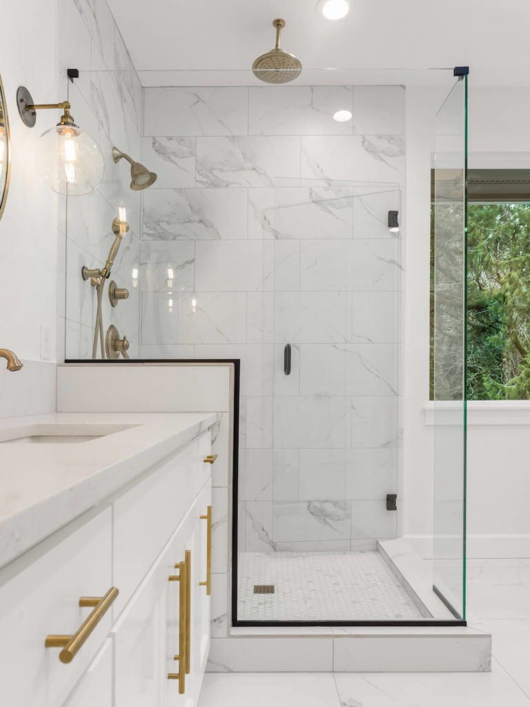 Bathroom Remodel with Marble Tile Gold Fixtures Frameless Glass Doors
