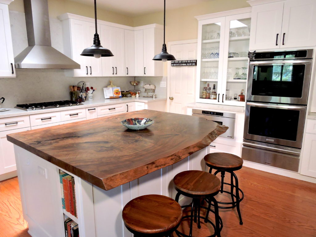 Ramona Kitchen Remodel with Solid Wood Kitchen Island Top, Wood Flooring, White Cabinets, Brushed Aluminum Stove Hood, Brushed Aluminum Oven with Tinted Glass,