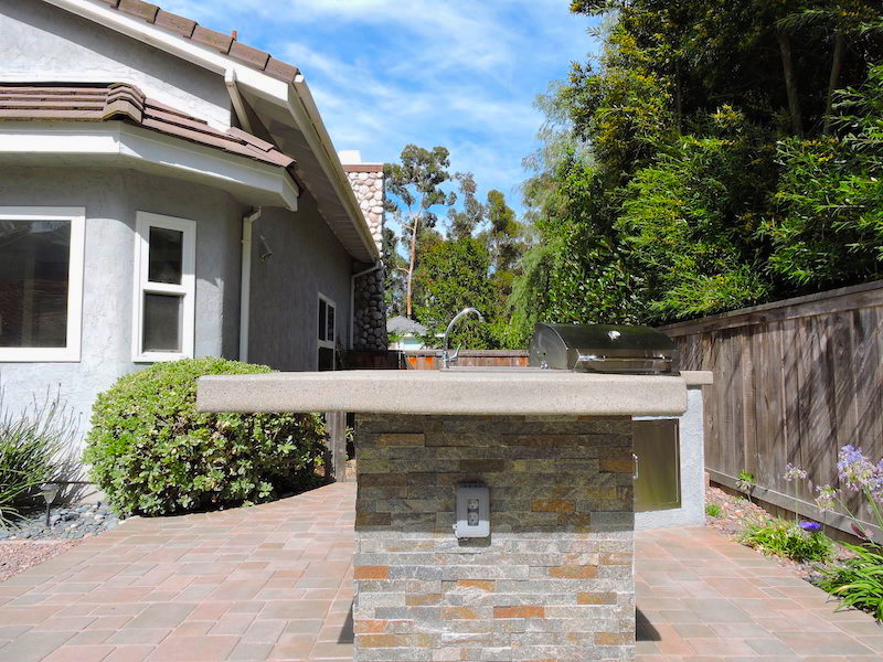 San Diego hardscape with Outdoor Kitchen, flagstone base, cement countertop, brushed aluminum grill, pavers, shrubs